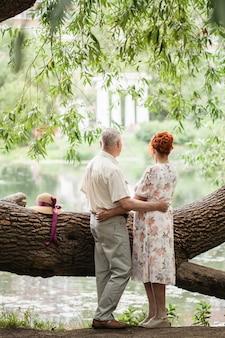Coppia di anziani che camminano nel parco, amanti, amore fuori dal tempo, passeggiate estive