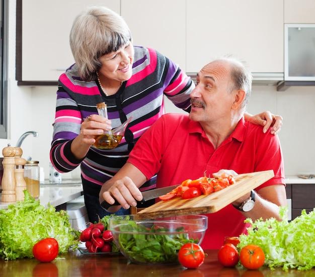 Coppia di anziani che cucina con pomodori