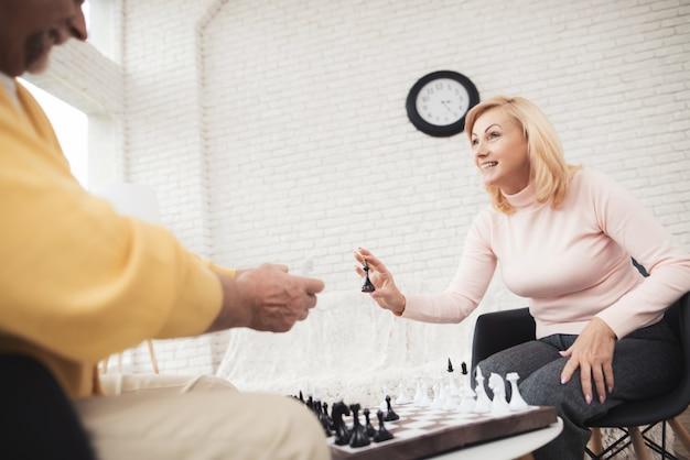 Coppia di anziani che giocano a scacchi a casa.