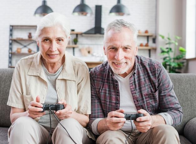 Coppia di anziani che giocano insieme ai videogiochi