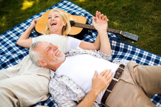 Coppia di anziani ridendo al picnic