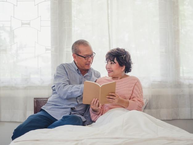 Coppia di anziani seduti a leggere un libro insieme a letto