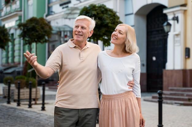 Coppia di anziani smiley facendo una passeggiata all'aperto in città