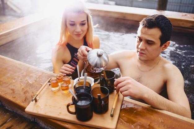 Coppia di bere il tè caldo mentre seduto in inverno al di fuori della spa calda