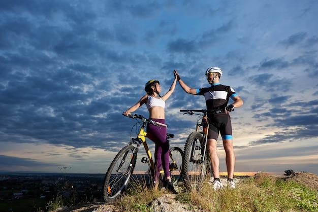 Coppia di ciclisti in cima a una montagna si danno il cinque contro un cielo nuvoloso al tramonto e una città nella valle