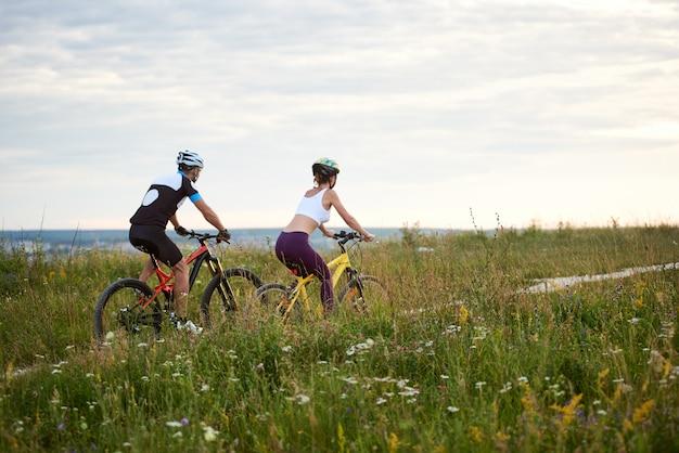 Coppia di ciclisti in sella a bici sul sentiero
