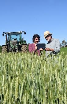 Coppia di contadini in un campo con una tavoletta digitale