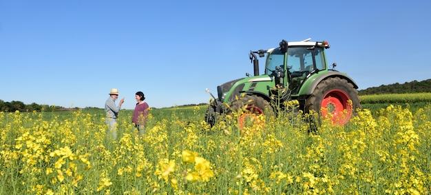 Coppia di contadini in un campo di colza con un trattore