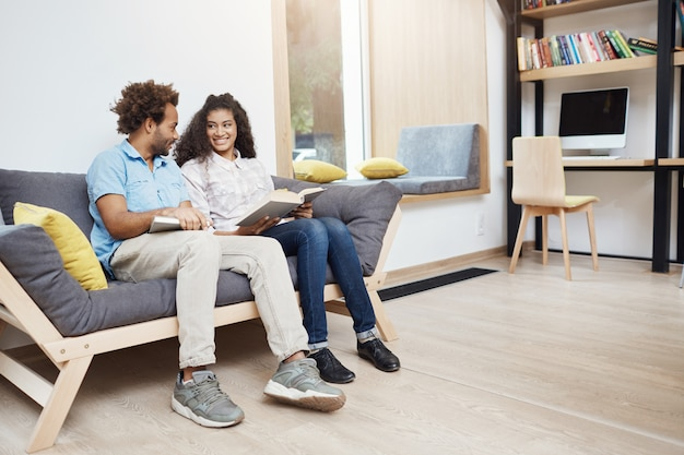 Coppia di due multietniche dalla pelle scura in una data in biblioteca. coppia seduta sul divano, leggendo libri preferiti, ridendo, trascorrendo del tempo comodo insieme