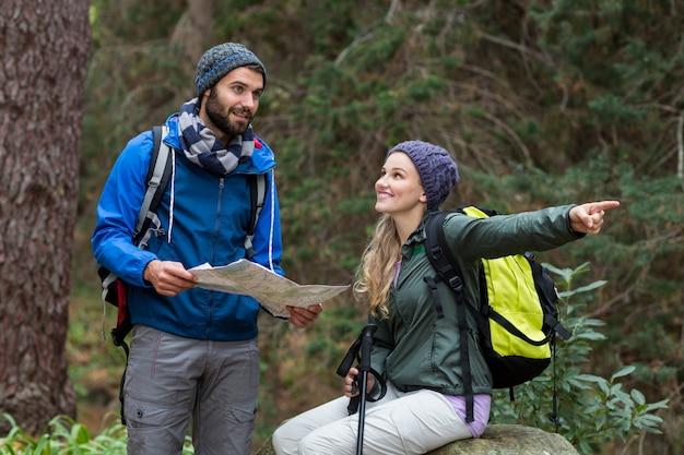 Coppia di escursionisti guardando la mappa e che punta lontano
