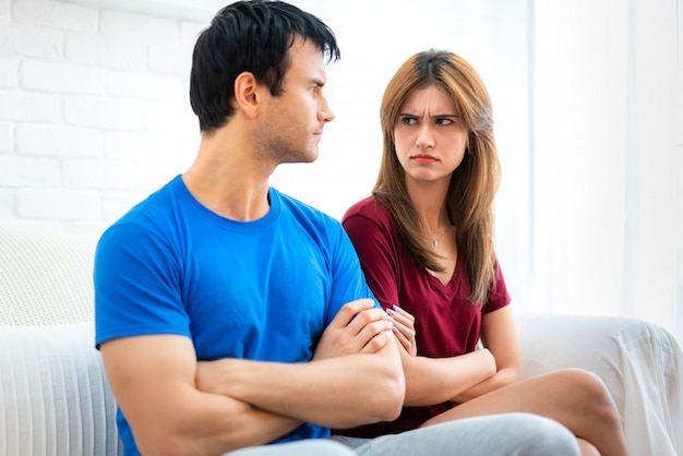 Coppia di famiglia seduta sul divano non parlando dopo una discussione, il giovane marito è stanco di una donna offesa che litiga costantemente voltando le spalle al fidanzato con le braccia incrociate.