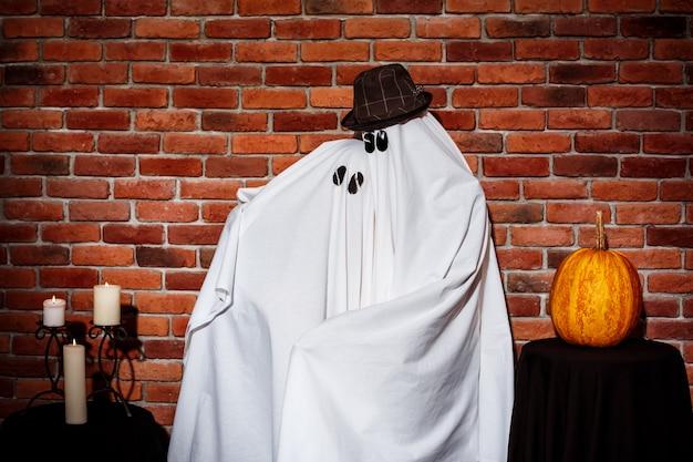 Coppia di fantasmi in posa sul muro di mattoni. festa di halloween.