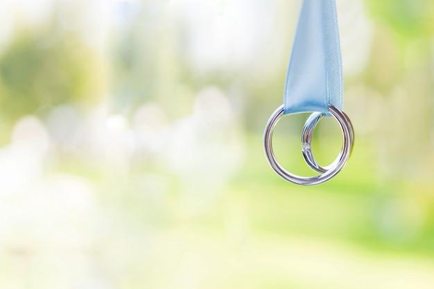 Coppia di fedi nuziali dorate con diamanti su nastri celesti.
