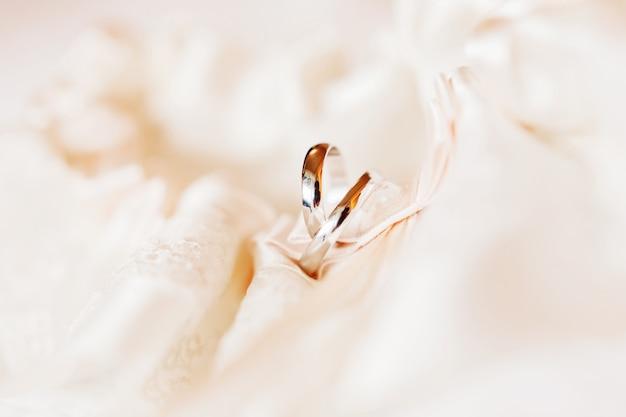 Coppia di fedi nuziali dorate su tessuto di pizzo di seta. simbolo di amore e matrimonio.