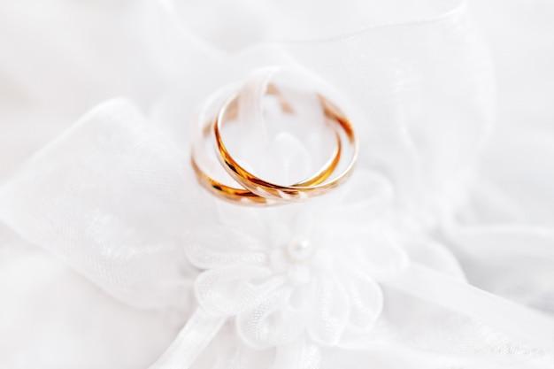 Coppia di fedi nuziali dorate su tessuto di seta di pizzo con fiore di stoffa.