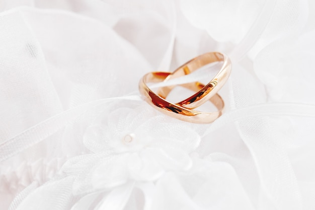 Coppia di fedi nuziali dorate su tessuto di seta in pizzo con fiore in tessuto. dettaglio del vestito da ricamo da sposa.