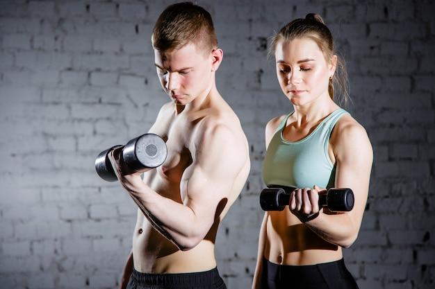 Coppia di fitness con attrezzature per allenamento con i pesi