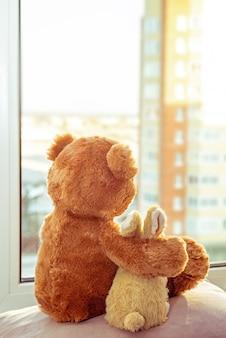 Coppia di giocattoli. coniglietto e orsacchiotto abbracciando amorevole orsacchiotto giocattolo e coniglietto seduto sul davanzale della finestra