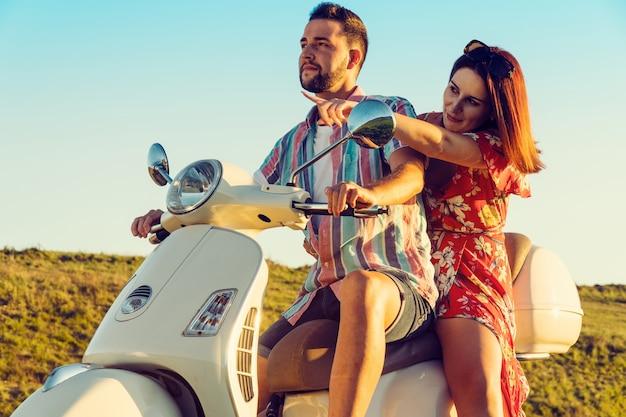 Coppia di giovani amici con vestiti freschi, divertirsi e sorridere su una moto