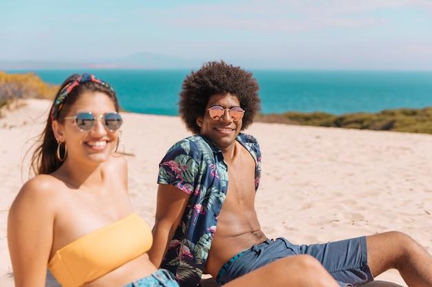 Coppia di giovani in occhiali da sole seduti sulla spiaggia, sorridendo e guardando fotocamera
