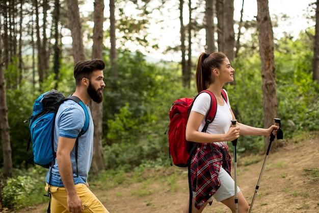 Coppia di giovani viaggiatori felici escursioni con gli zaini sulla bellissima pista forestale
