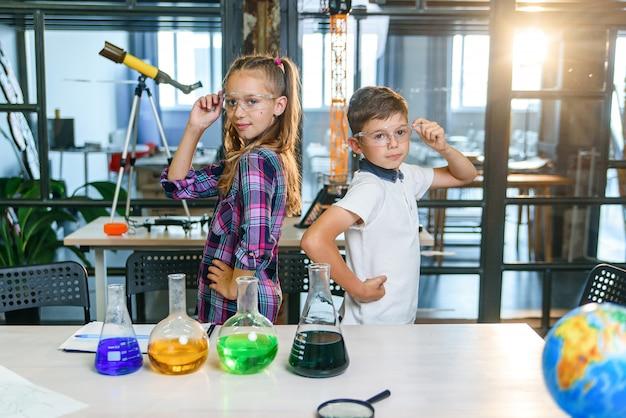Coppia di graziose pupille in occhiali protettivi sorridenti in piedi con le braccia incrociate schiena contro schiena in classe chimica alla scuola elementare.