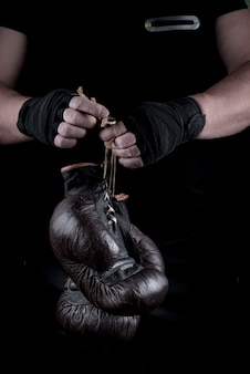 Coppia di guanti sportivi da boxe molto vecchi nelle mani degli uomini