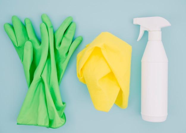 Coppia di guanti verdi; tovagliolo e bottiglia spray bianco su sfondo blu