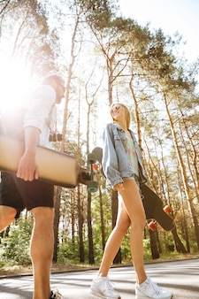 Coppia di innamorati camminando con skateboard all'aperto. guardando da parte.
