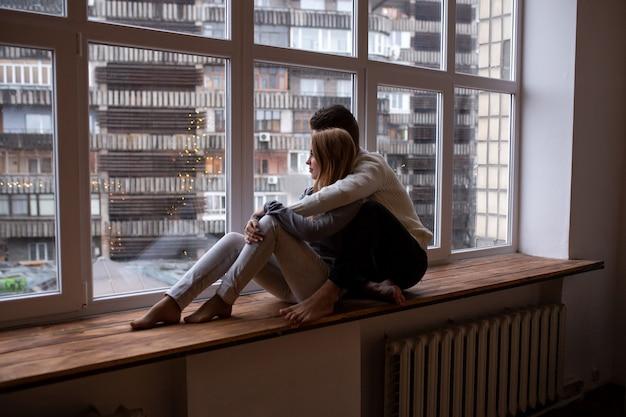 Coppia di innamorati che abbraccia e si diverte nella loro camera da letto vicino alla finestra