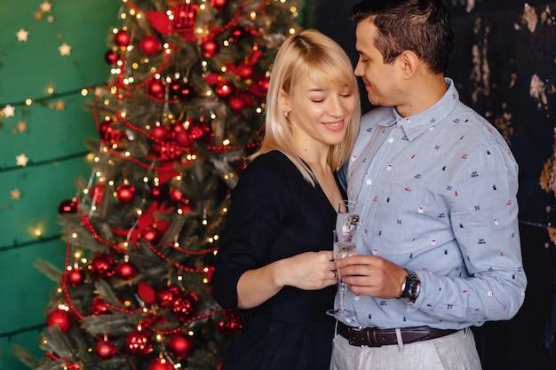 Coppia di innamorati con bicchieri di champagne sullo sfondo di un albero di natale