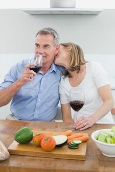 Coppia di innamorati con bicchieri di vino in cucina