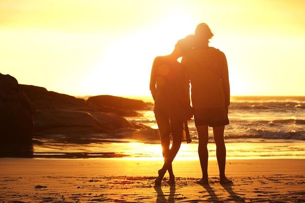 Coppia di innamorati in piedi sulla spiaggia guardando il tramonto