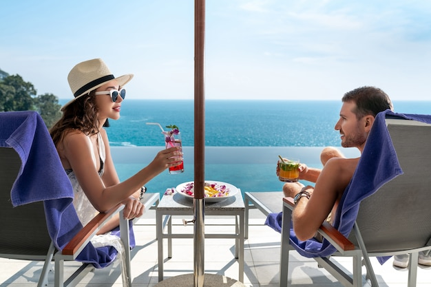 Coppia di innamorati in un resort tropicale. l'uomo e la donna si guardano seduti sulle sdraio a bordo piscina e si godono i cocktail.