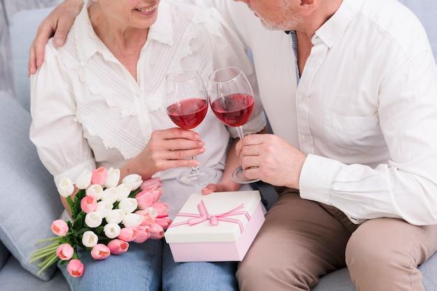 Coppia di innamorati seduti sul divano con bicchieri di vino; confezione regalo e bouquet di fiori di tulipano