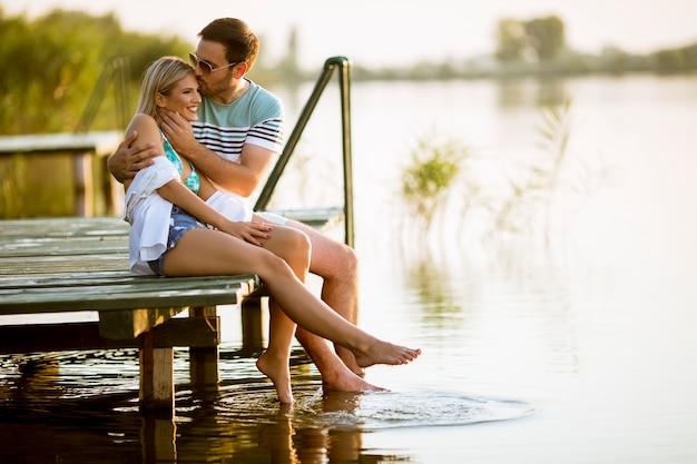 Coppia di innamorati seduti sul molo sul lago