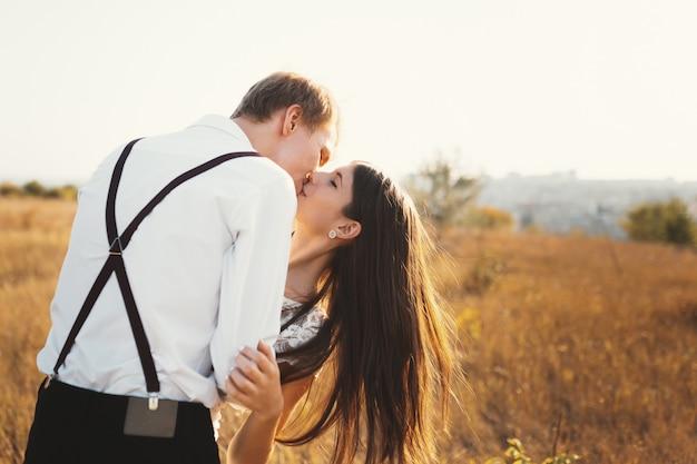Coppia di innamorati vestita di bianco baciare all'aperto, toccante, gentile