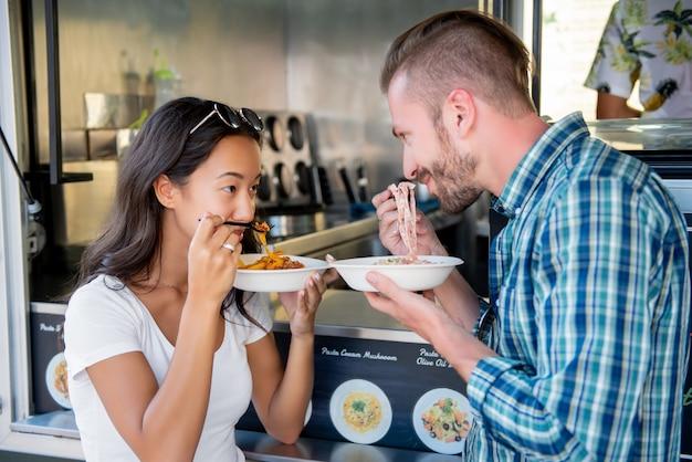 Coppia di mangiare la pasta al camion di cibo