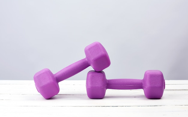 Coppia di manubri in plastica viola per sport su un bianco in legno