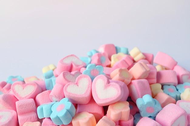 Coppia di marshmallow a forma di cuore rosa e bianco sul mucchio di caramelle marshmallow a forma di fiore