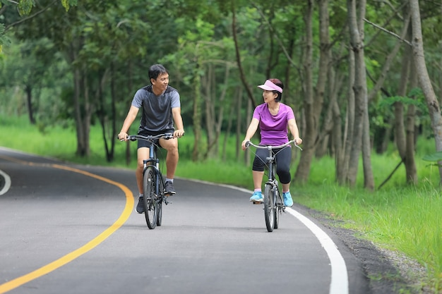 Coppia di mezza età rilassante esercizio con la bicicletta nel parco