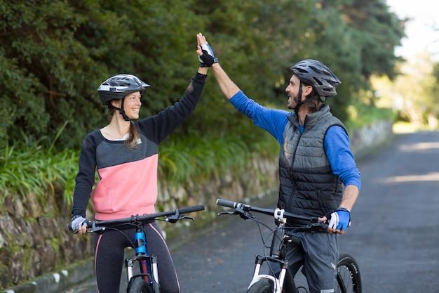 Coppia di motociclisti dando il cinque mentre si va in bicicletta sulla strada