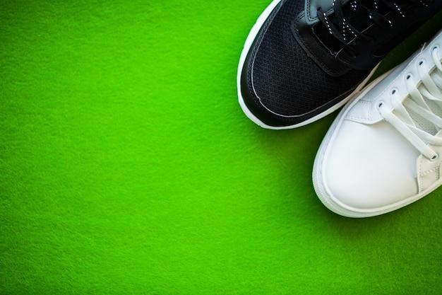 Coppia di nuove sneakers eleganti su sfondo verde.