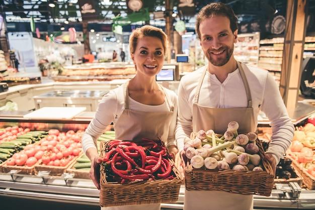 Coppia di operai del supermercato tiene in mano delle verdure.