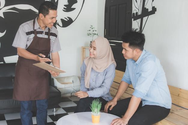 Coppia di ordinare cibo al cameriere