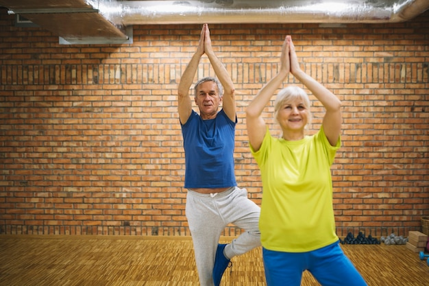 Coppia di pensionati allenandovi in palestra
