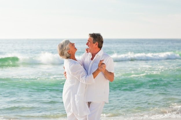 Coppia di pensionati che ballano sulla spiaggia