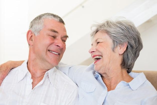 Coppia di pensionati seduti sul divano sorridendo a vicenda
