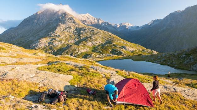 Coppia di persone che installano una tenda da campeggio sulle montagne, lasso di tempo. avventure estive sulle alpi, lago idilliaco e vetta.