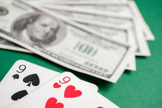 Coppia di picche e cuori nove durante il poker con dollari sul tavolo verde.